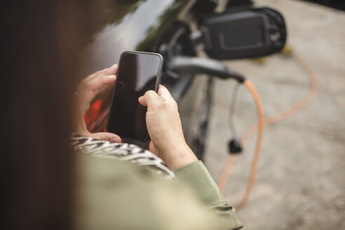 Midsection of woman using smart phone while standing by charging electric car - MASF11425
