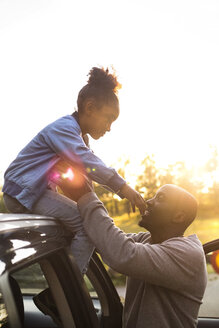 Smiling man assisting girl in getting down from car roof against clear sky during sunset at park - MASF11428