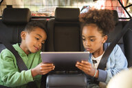 Siblings sharing digital tablet while sitting in electric car - MASF11434