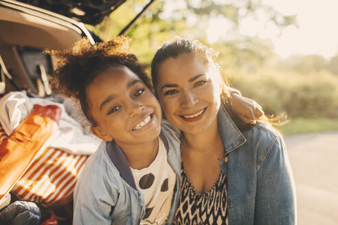 Portrait of smiling girl with arm around mother sitting in car trunk during picnic - MASF11437