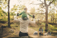 Man carrying son shoulders during picnic with family in public park - MASF11440