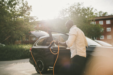 Mid adult man holding electric cable by car on driveway - MASF11446