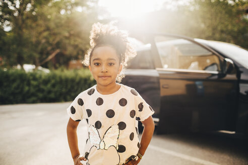 Portrait of girl standing against electric car on driveway - MASF11449