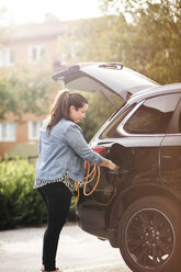Side view of woman charging electric car on driveway - MASF11455