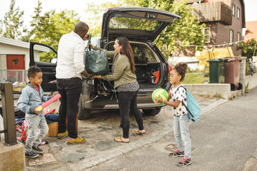 Siblings playing while parents loading luggage in car trunk on driveway - MASF11461