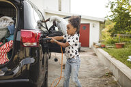 Girl charging electric car while standing on driveway - MASF11464