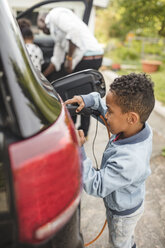 Side view of boy charging electric car while standing on driveway - MASF11467