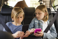 Blond siblings using smart phones while sitting in car - MASF11470