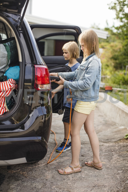 Full length of siblings charging electric car on driveway - MASF11473