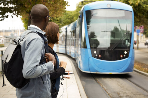 Commuters waiting on sidewalk while looking at blue tram in city - MASF11479