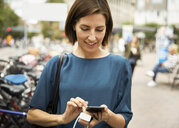 Smiling mid adult businesswoman using smart phone while standing in city - MASF11482