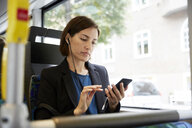 Mid adult female commuter using smart phone while sitting in bus - MASF11485