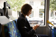 Side view of businesswoman using smart phone while sitting in bus - MASF11488
