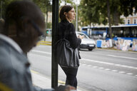 Businesswoman looking away while standing at bus stop with commuter in city - MASF11491