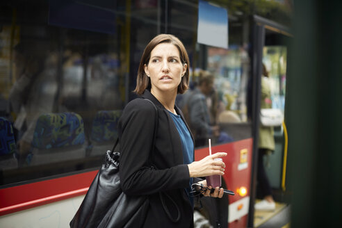 Confident businesswoman looking away while standing with drink against bus in city - MASF11494
