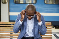 Businessman adjusting in-ear headphones while sitting at railroad station - MASF11500