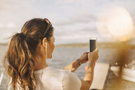 Woman taking selfie through mobile phone against lake during summer vacation - MASF11512