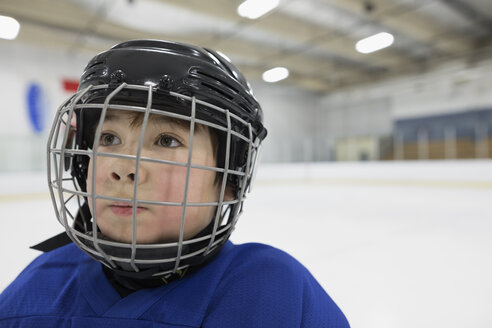 Close up serious boy ice hockey player in helmet looking away on ice hockey rink - HEROF23635