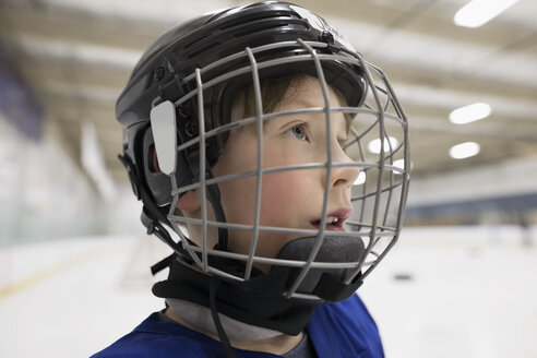 Close up serious boy ice hockey player in helmet looking away on ice hockey rink - HEROF23638