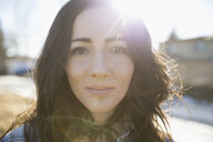 Close up portrait sun shining behind confident brunette woman - HEROF23650