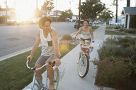 Couple riding beach cruiser bicycles on summer sidewalk - HEROF23761