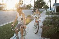Couple riding beach cruiser bicycles on summer sidewalk - HEROF23761