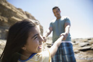 Carefree Latino father and daughter holding hands on sunny beach - HEROF23782