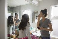 Daughter watching mother applying makeup in bathroom mirror - HEROF23785