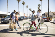 Couples walking on sunny California street with bicycle on crosswalk - HEROF23797