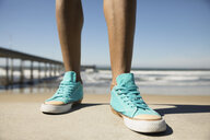 Close up man wearing turquoise sneakers on sunny California beach - HEROF23800