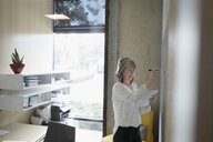 Businesswoman with digital tablet brainstorming at whiteboard in office - HEROF23821