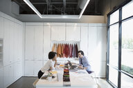 Designers discussing fabric swatches in conference room meeting - HEROF23830