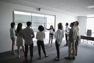 Businesswoman leading presentation at projection screen in conference room meeting - HEROF23845