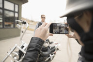 Female biker with camera phone photographing man at motorcycle in parking lot - HEROF23872