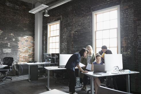 Creative business people meeting at laptop in open plan loft office - HEROF23896