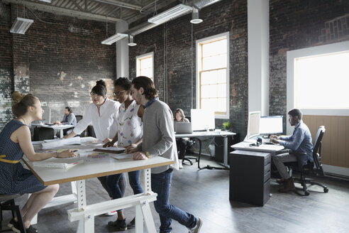 Creative business people meeting at table in open plan loft office - HEROF23917