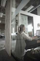 Creative businesswoman working at laptop in conference room - HEROF23932