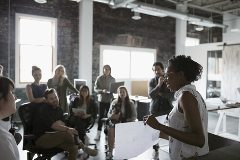Female architect with blueprint leading meeting in open plan loft office - HEROF23986