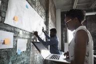 Creative business people with laptop brainstorming in meeting - HEROF23992