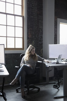Creative businesswoman working at laptop in office - HEROF24010