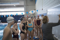 Female coach at whiteboard coaching swimming team at practice - HEROF24013