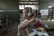 Female boxer listening to music with headphones in boxing ring at gym - HEROF24028