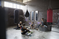 Female boxers resting, eating snack post workout at gritty gym with punching bags - HEROF24037