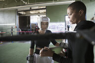 Female boxer training woman, using digital tablet in boxing ring - HEROF24046