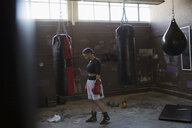 Female boxer at punching bag in gritty gym - HEROF24052
