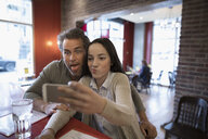Father and teenage daughter taking selfie at diner counter - HEROF24058