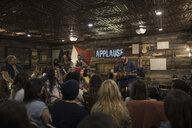 Audience listening to musician playing guitar and singing on garage stage - HEROF24118
