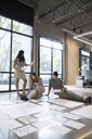 Architects with laptop reviewing blueprints on office floor - HEROF24214