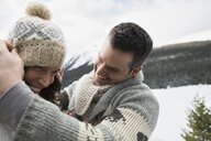 Playful couple wearing warm clothing in snow - HEROF24226