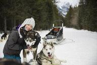 Portrait of girl hugging dogsled dog in snow - HEROF24247